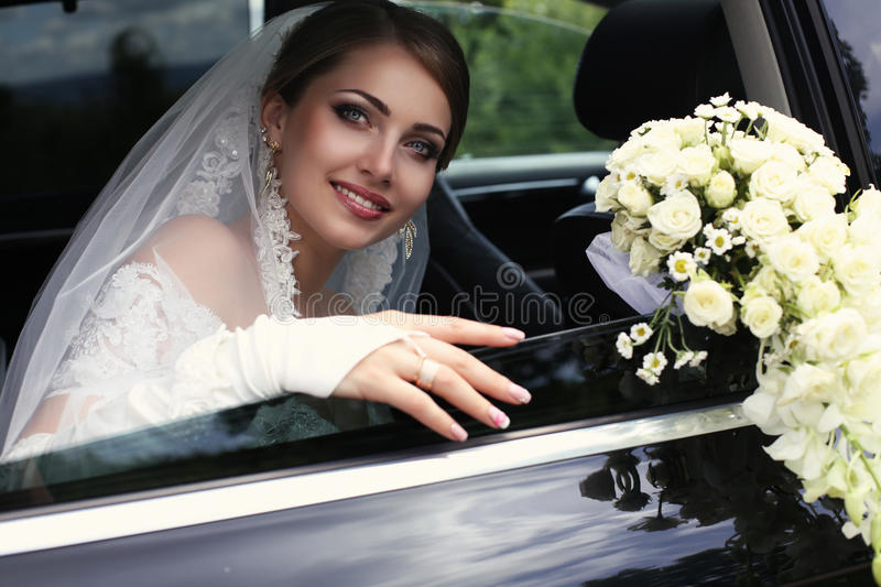 Gorgeous bride in wedding dress with bouquet of flowers posing in car stock image