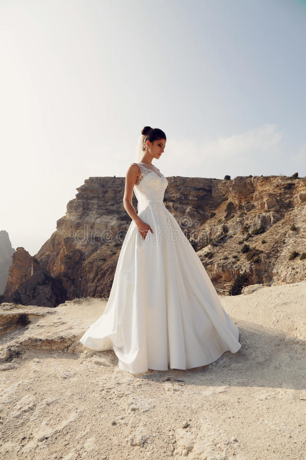 Gorgeous bride in wedding dress posing on sea cost. Fashion outdoor photo of beautiful bride. posing on sea cost stock photos