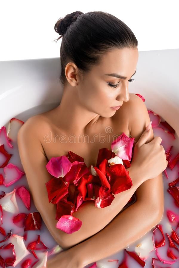 Gorgeous brunette in bath wth rose petals royalty free stock images