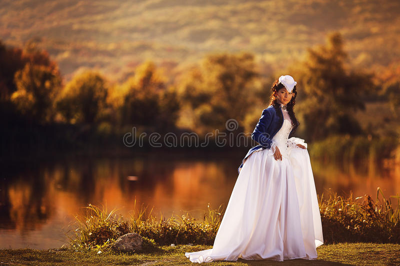 Gorgeous brunette beauty in a old-fashioned dress stock photography