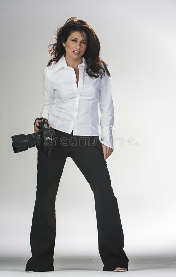 Gorgeous Brunette Ethnic Model Poses In A Studio Environment With Camera Equipment. A beautiful ethnic brunette model posing in a studio environment with camera royalty free stock images