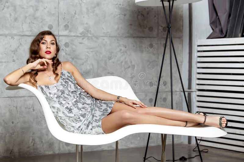 Gorgeous brunette girl in a wonderful gray evening dress is laying in a stylish white armchair against the gray wall royalty free stock photos