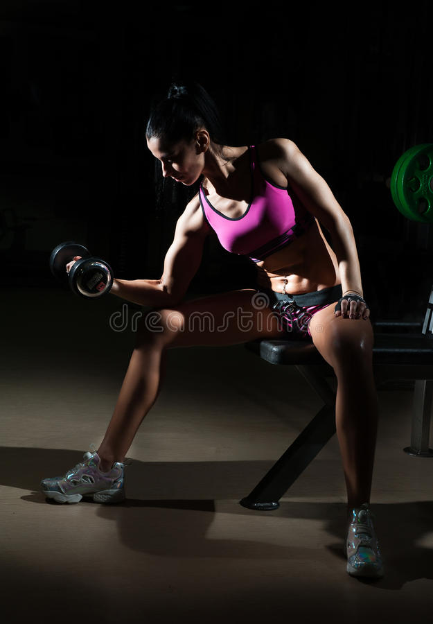 Gorgeous brunette lifting some weights and working on her biceps in a gym. Fitness woman doing workout. Sporty girl doing exercise. In fitness center. Beautiful stock photos