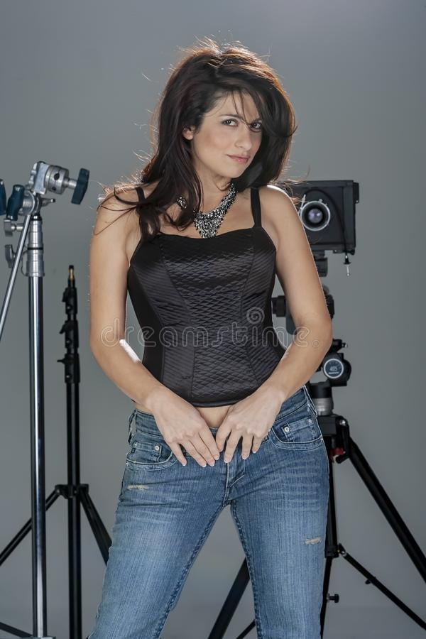 Gorgeous Brunette Model Poses In A Studio Environment Against A White Background Holding Camera Equipment. A beautiful brunette model posing in a studio stock photography