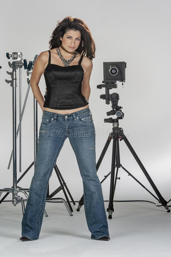 Gorgeous Brunette Model Poses In A Studio Environment Against A White Background Holding Camera Equipment. A beautiful brunette model posing in a studio royalty free stock photography
