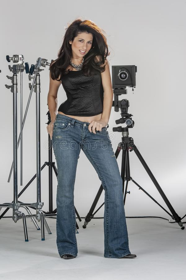 Gorgeous Brunette Model Poses In A Studio Environment Against A White Background Holding Camera Equipment. A beautiful brunette model posing in a studio stock images