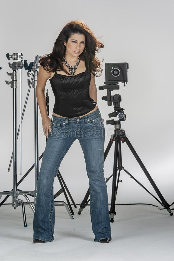 Gorgeous Brunette Model Poses In A Studio Environment Against A White Background Holding Camera Equipment. A beautiful brunette model posing in a studio stock image