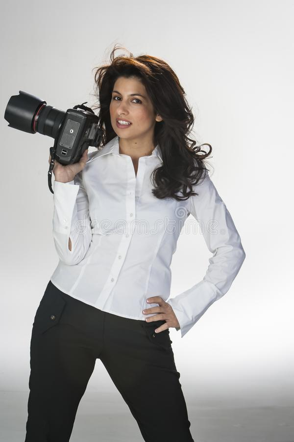 Gorgeous Brunette Model Poses In A Studio Environment Against A White Background Holding Camera Equipment stock photography