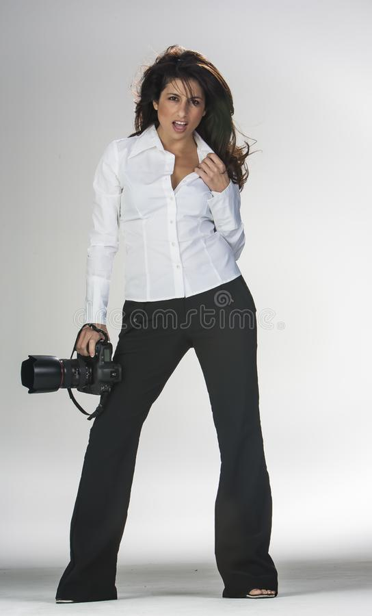 Gorgeous Brunette Model Poses In A Studio Environment Against A White Background Holding Camera Equipment stock image