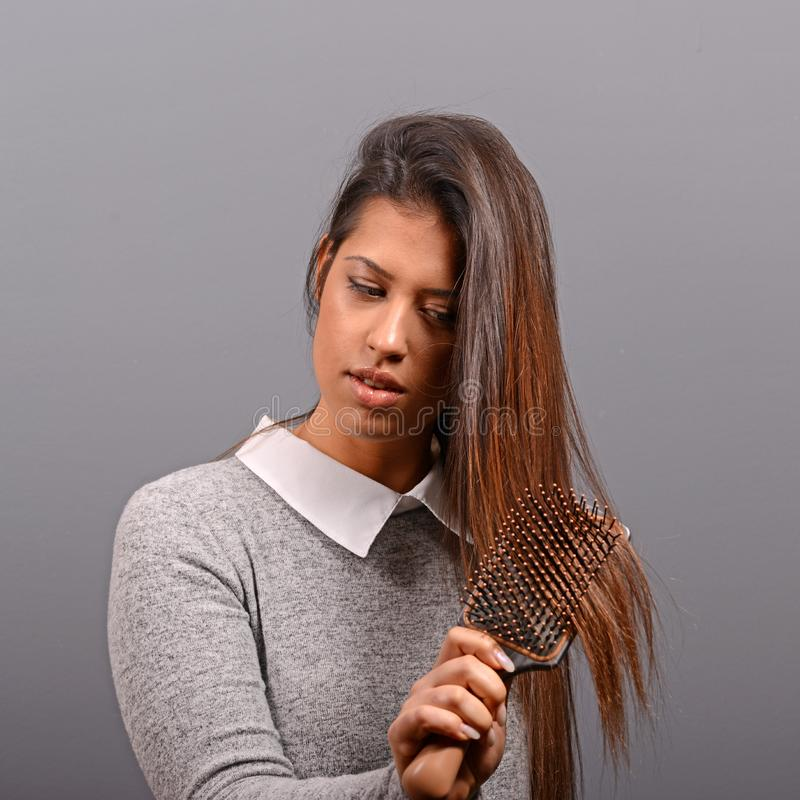 Gorgeous brunette woman brushing her healthy hair against gray background royalty free stock photography