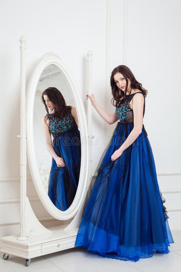 Gorgeous brunette woman in fashionable dress posing near big mirror at white room and looking at camera and smiling royalty free stock images