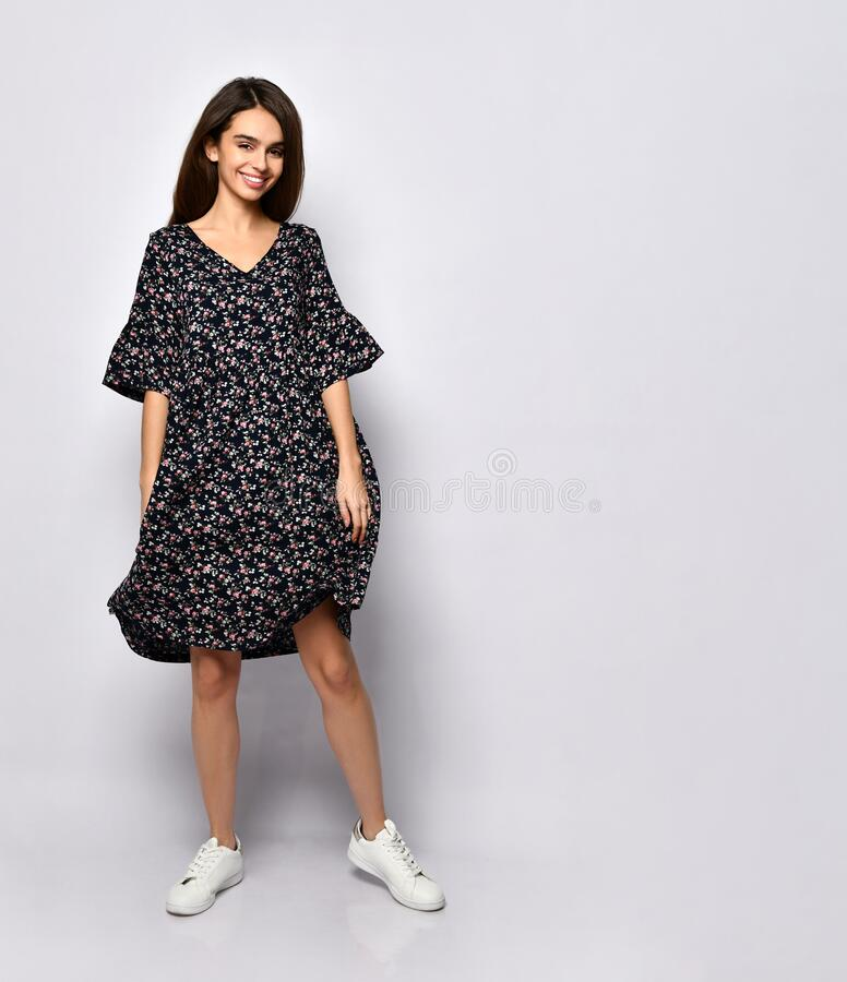 Gorgeous brunette woman in black dress with floral print and white sneakers. She smiling, posing isolated on white. Full length. Gorgeous brunette woman with royalty free stock photo