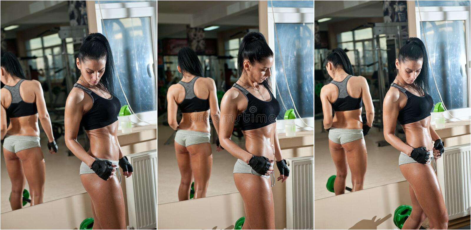 Gorgeous brunette working on her muscles in a gym, mirror reflection. Fitness woman doing workout. Sporty girl doing exercise. In fitness center. Beautiful stock photo