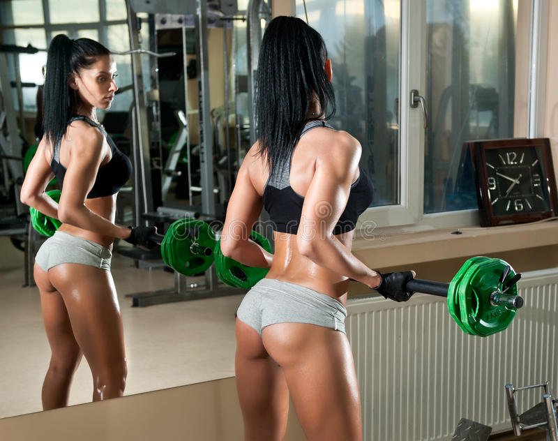 Gorgeous brunette working on her muscles in a gym, mirror reflection. Fitness woman doing workout. Sporty girl doing exercise. In fitness center. Beautiful stock photography