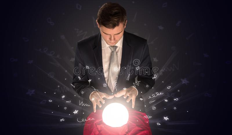 Businessman looking to inspiration in a magic ball and doodle concept stock photo