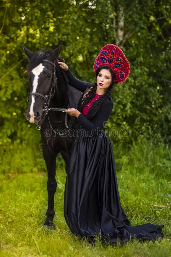 Gorgeous Caucasian Model in Russian Kokoshnik Holding Thoroughbred Horse Against Nature Background royalty free stock images