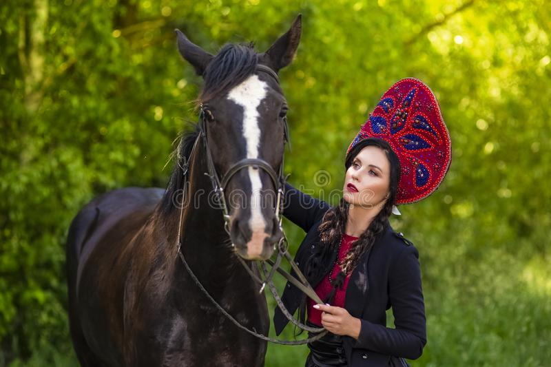 Gorgeous Caucasian Model in Russian Kokoshnik Holding Thoroughbred Horse Against Nature Background. Horizontal Image Composition royalty free stock images