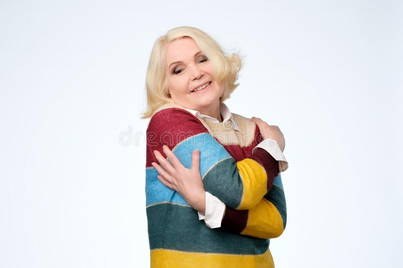 Senior woman having pleased happy facial expression, embracing herself stock photo