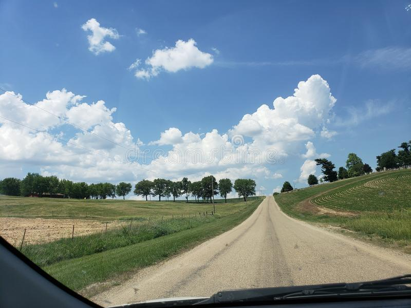 Gorgeous clouds on a country road stock photos