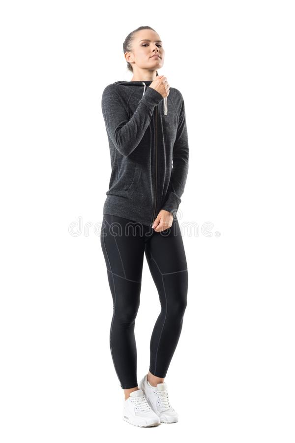 Gorgeous confident sporty woman zipping zip up hooded sweatshirt looking at camera. royalty free stock photos