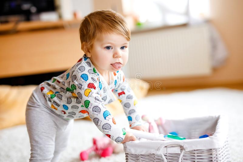 Gorgeous cute beautiful little baby girl playing with educational toys at home or nursery. Happy healthy child learning. Crawling and standing royalty free stock photos