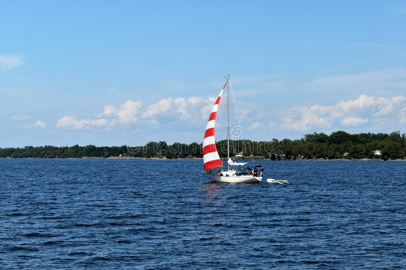 Red and White Sail Boat on Lake Champlain, New York, United States, US. USA. A gorgeous sunny day for a sail on a sailboat with a red and white sail on Lake royalty free stock images