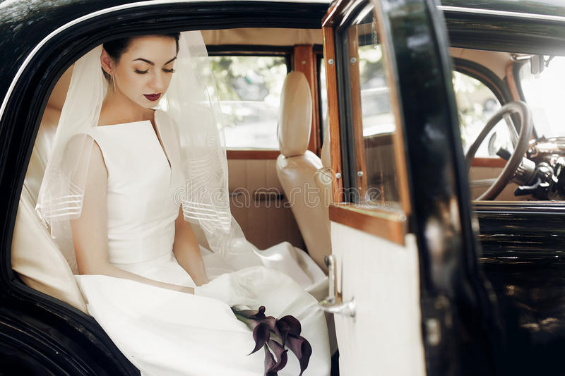 gorgeous elegant bride posing in stylish retro black car, sitting inside in saloon holding bouquet of callas. luxury wedding in v royalty free stock photography