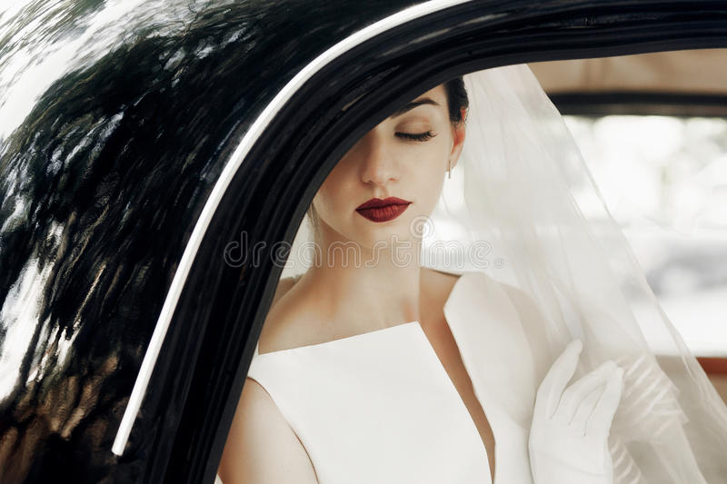 gorgeous elegant bride posing in stylish retro black car, sitting inside in saloon. luxury wedding in vintage style. portrait royalty free stock image