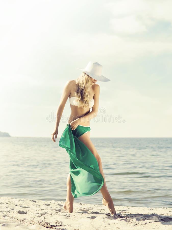 Beautiful, attractive, young woman in a hat and white bikini with green silk on a beach. Resort, vacation, concept. royalty free stock photos