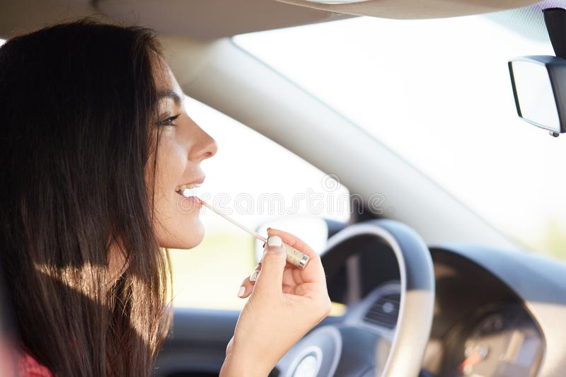 Gorgeous elegant young female uses mirror in car to appy lipstick on lips, cares of her beauty, has time for make up while being s royalty free stock image