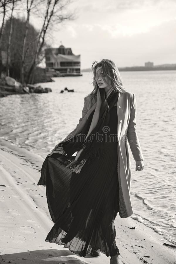 Gorgeous european woman in warm coat and dress on a walk in park near river. Windy weather. Her clothes fly in the wind. Sad,. Sensual and thughtful expression royalty free stock images