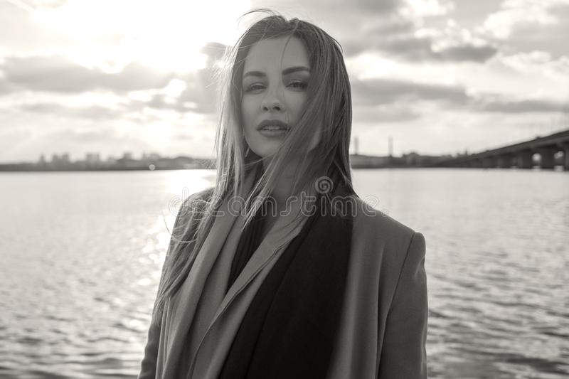 Gorgeous european woman in warm coat and dress on a walk in park near river. Windy weather. Her clothes fly in the wind. Sad,. Sensual and thughtful expression stock photos