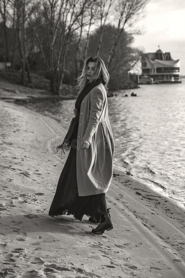 Gorgeous european woman in warm coat and dress on a walk in park near river. Windy weather. Her clothes fly in the wind. Sad,. Sensual and thughtful expression stock photography