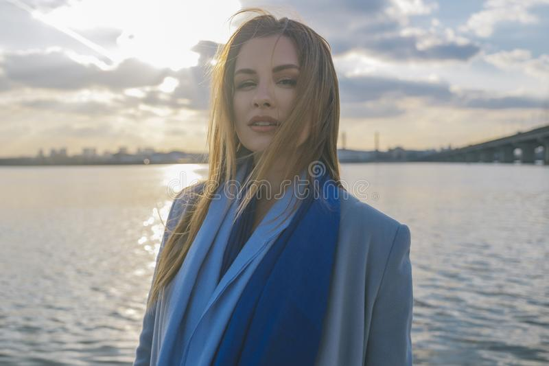Gorgeous european woman in warm coat and dress on a walk in park near river. Windy weather. Her clothes fly in the wind. Sad,. Sensual and thughtful expression royalty free stock photo