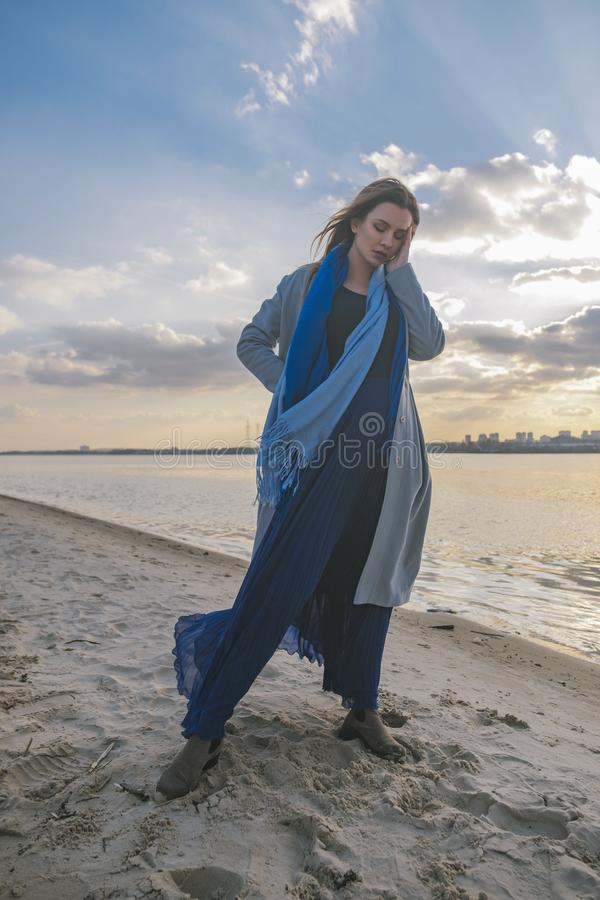 Gorgeous european woman in warm coat and dress on a walk in park near river. Windy weather. Her clothes fly in the wind. Sad, stock images