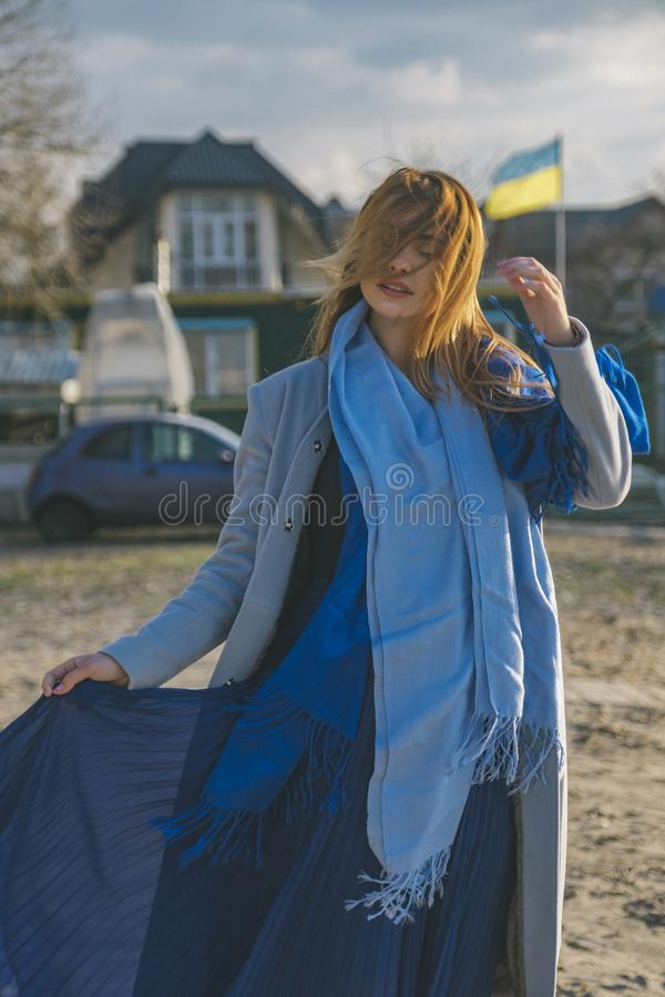 Gorgeous european woman in warm coat and dress on a walk in park near river. Windy weather. Her clothes fly in the wind. Sad, royalty free stock images