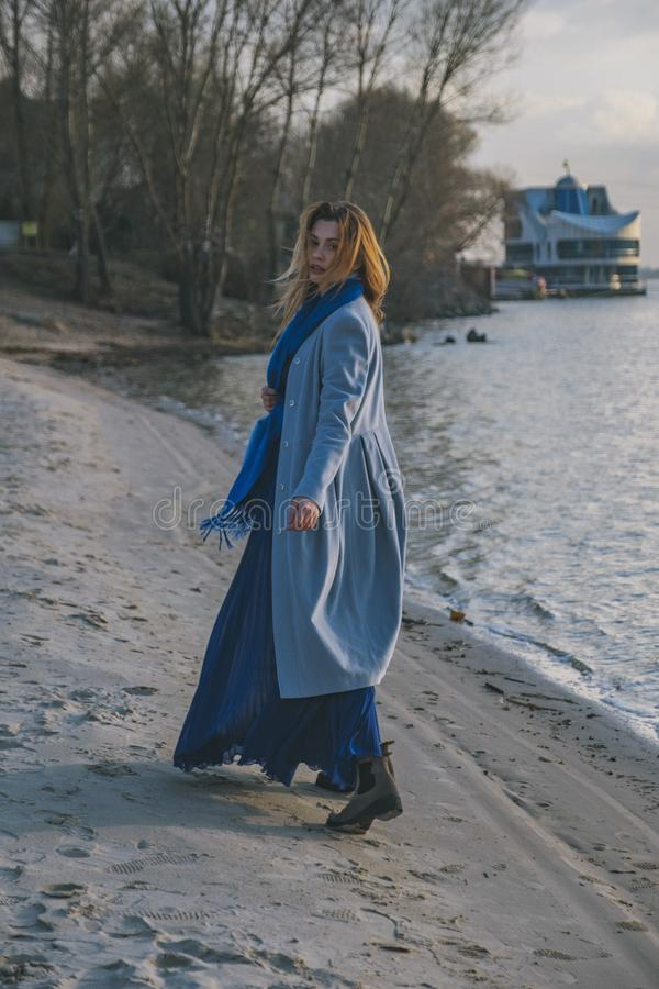 Gorgeous european woman in warm coat and dress on a walk in park near river. Windy weather. Her clothes fly in the wind. Sad,. Sensual and thughtful expression stock image