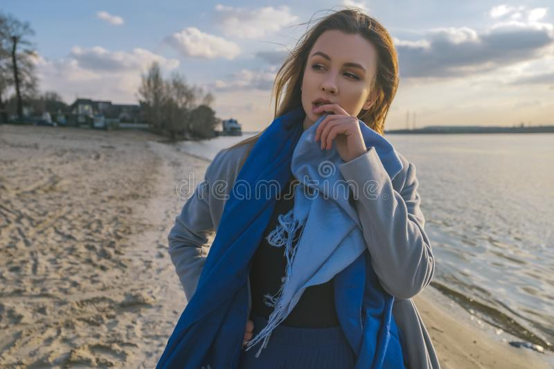 Gorgeous european woman in warm coat and dress on a walk in park near river. Windy weather. Her clothes fly in the wind. Sad,. Sensual and thughtful expression royalty free stock image