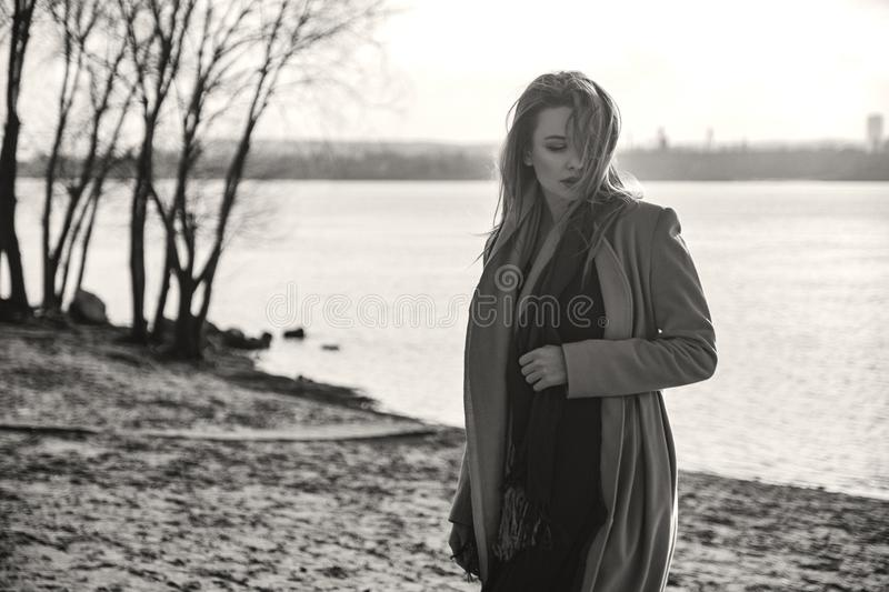 Gorgeous european woman in warm coat and dress on a walk in park near river. Windy weather. Her clothes fly in the wind. Sad, royalty free stock photography