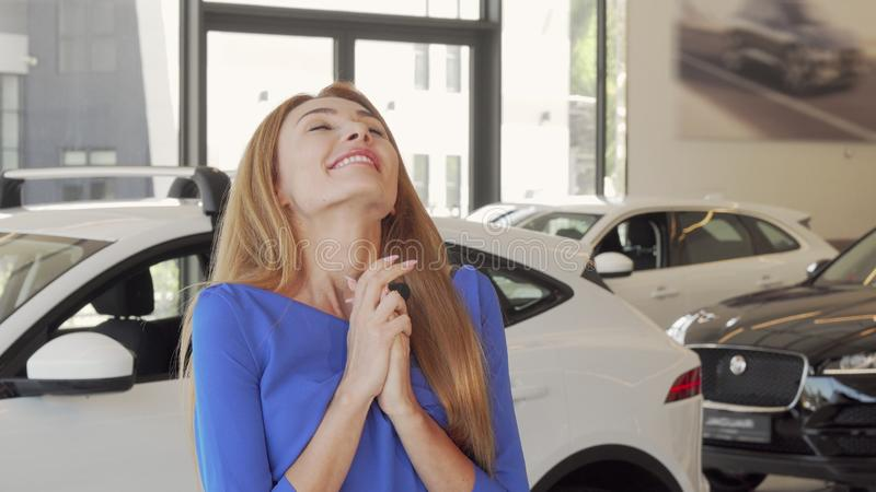 Gorgeous excited woman celebrating buying new car at the dealership stock images