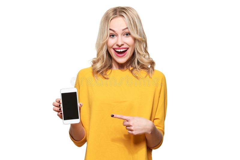 Gorgeous excited woman pointing to blank screen on mobile phone over white background, celebrating victory and success. Excitement. Cheering emotion stock photography