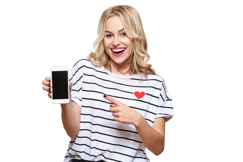 Gorgeous excited woman pointing to blank screen on mobile phone over white background, celebrating victory and success. Excitement, cheering emotion stock photos