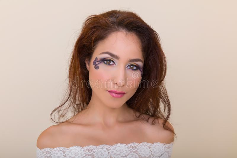 Gorgeous eyes. Young brunette fashion model with colorful extravagant eye make-up stock photography