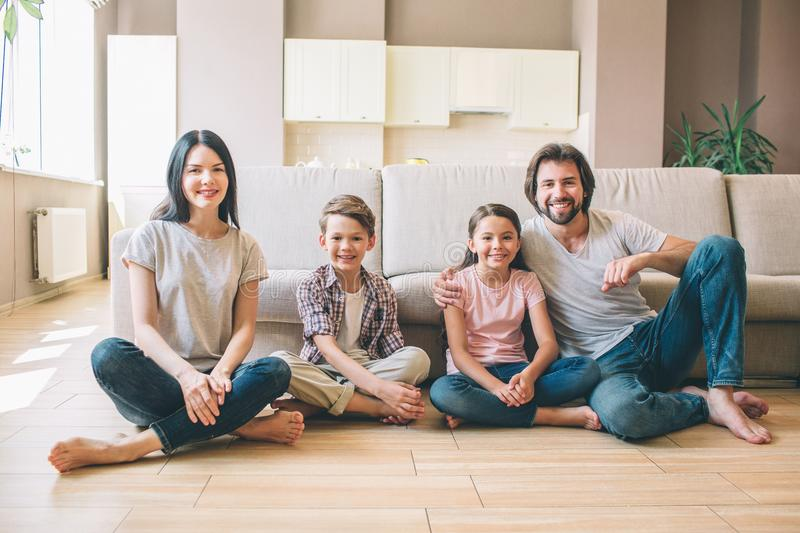 Gorgeous family are sitting on the floor with their legs grossed and looking on camera. They smile. Guy is leaning to. Sofa. They wear shirts and jeans royalty free stock photos