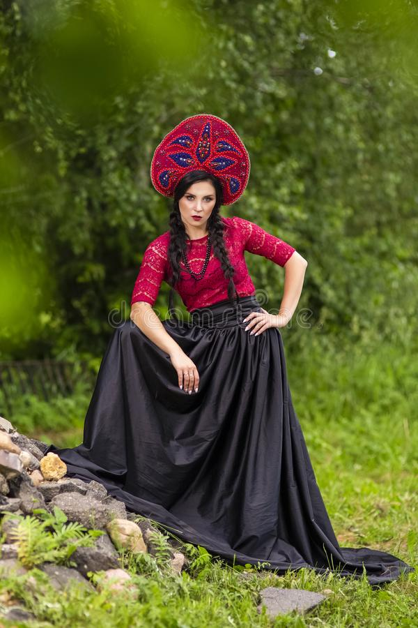 Gorgeous Fashion Brunete Woman In Russian Style Kokoshnik Outdoors Against Batch of Stones. Vertical Orientation royalty free stock photography