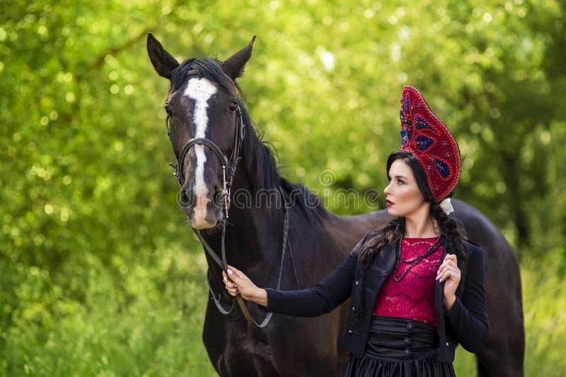 Gorgeous Fashion Caucasian Model in Kokoshnik Posing With Thoroughbred Horse Against Nature Background Outdoors. Horizontal Image stock image