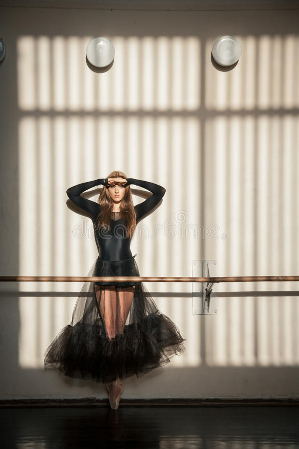 Gorgeous female ballet dancer standing at the wall royalty free stock photography