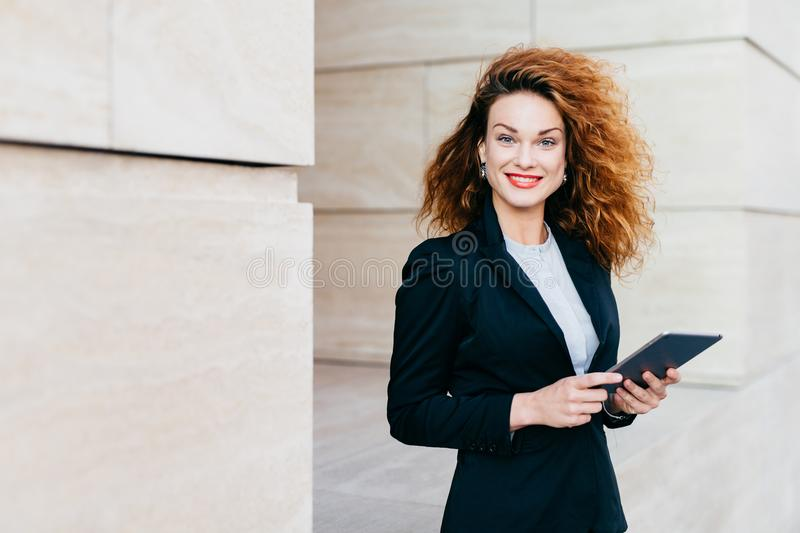 Gorgeous female in black suit, having curly bushy hair, blue eyes and red painted lips smiling pleasantly while typing text messag royalty free stock photos