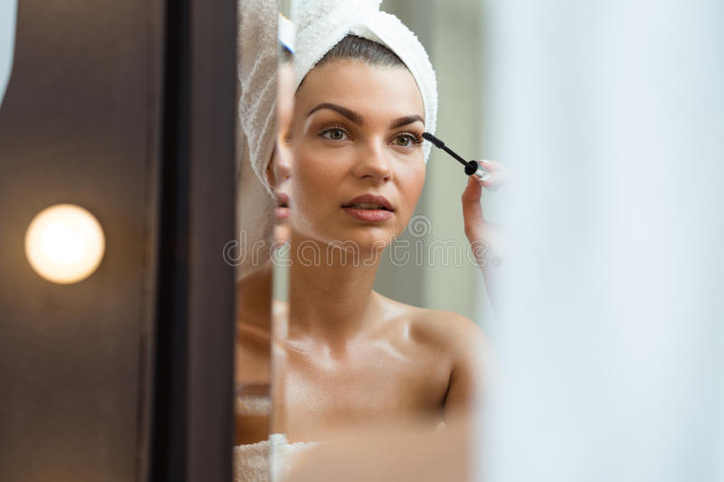 Gorgeous female putting makeup stock images