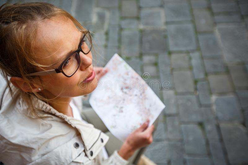 Gorgeous female tourist with a map discovering a foreign city s. Hallow DOF; color toned image royalty free stock image